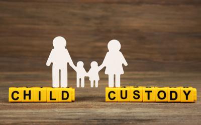 Paper cut out of a family standing on yellow block letters that spell child custody