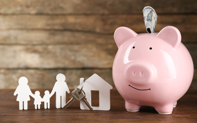 Photograph of a piggy bank, paper cut out of a family of four and a house with a key hanging off the chimney